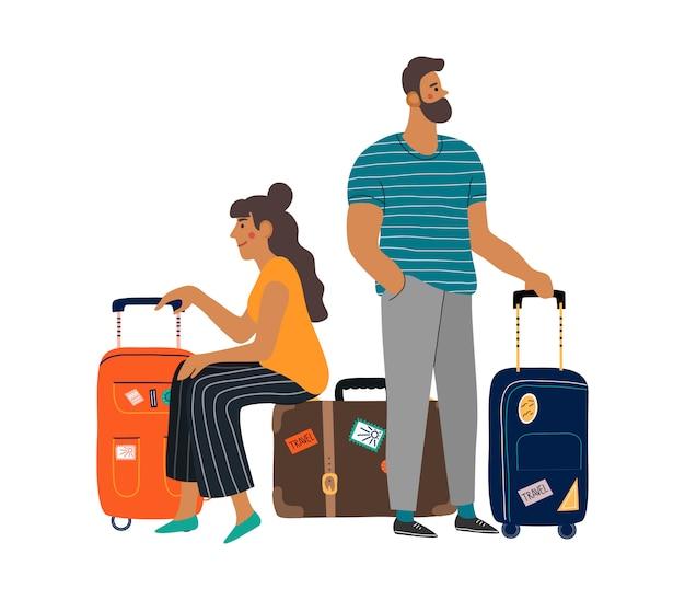スーツケースを持って待っている男女。