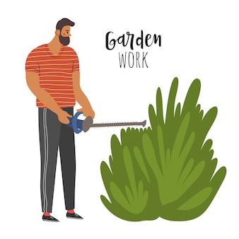 男性の農夫が生け垣のために茂みを刈っています。