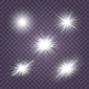Набор белого светящегося света взрывается на прозрачном фоне сверкающие магические частицы пыли. звезда взорвалась блестками. золотой глиттер яркая звезда. прозрачное сияющее солнце, яркая вспышка