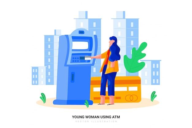Молодая женщина с помощью банкомата