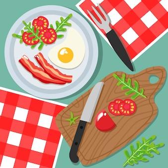 Вид сверху на стол, тарелка с яйцами, беконом, салатом и помидорами. разделочная доска с нарезанным помидором, ножом и вилкой.
