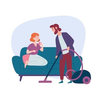 床に掃除機をかける男、ソファに座っている女性。