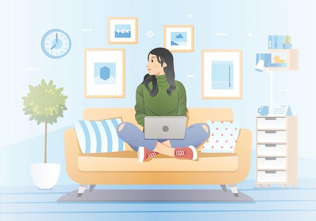 Молодая девушка работает дома, сидя в диване и ноутбук на коленях с гостиной интерьер в качестве фона