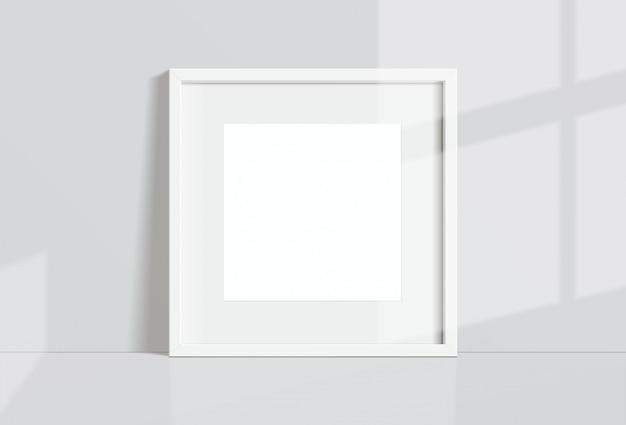 窓の光と影で白い壁に掛かっている最小限の空の正方形の白いフレーム画像。イラストを分離します。