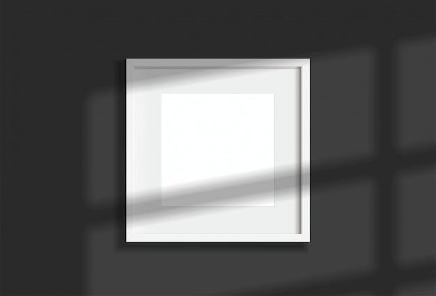 窓の光と影で暗い壁に掛かっている最小限の空の正方形の白いフレーム画像。イラストを分離します。