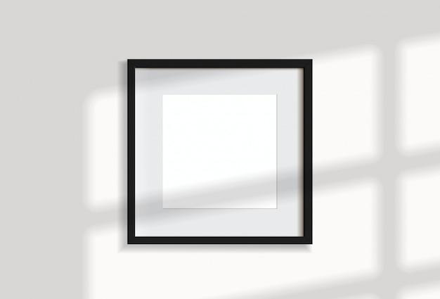 窓の光と影で白い壁に掛かっている最小限の空の正方形の黒いフレーム画像。イラストを分離します。