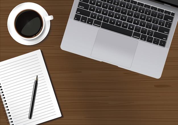 ラップトップノートペンとコーヒーカップの木製テーブルワークスペース