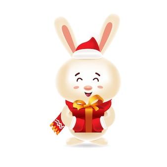 赤い帽子と分離されたクリスマスのギフトボックスを運ぶ赤いスカーフかわいいウサギ