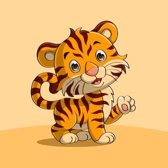 Милый тигренок машет рукой