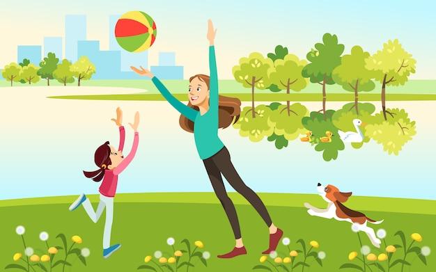 ママと娘は公園の湖でボールをプレー犬と