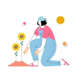 女性は春に太陽の下でヒマワリを育てます