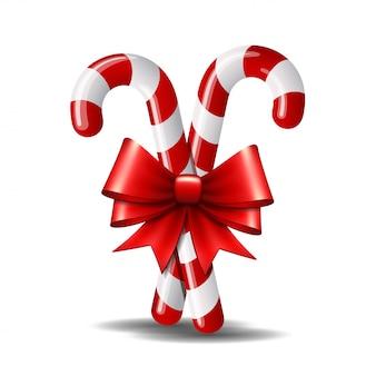 白で隔離される赤の弓とクリスマスキャンデー杖