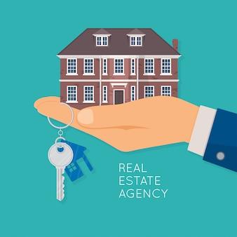 Рука держит дом и ключ