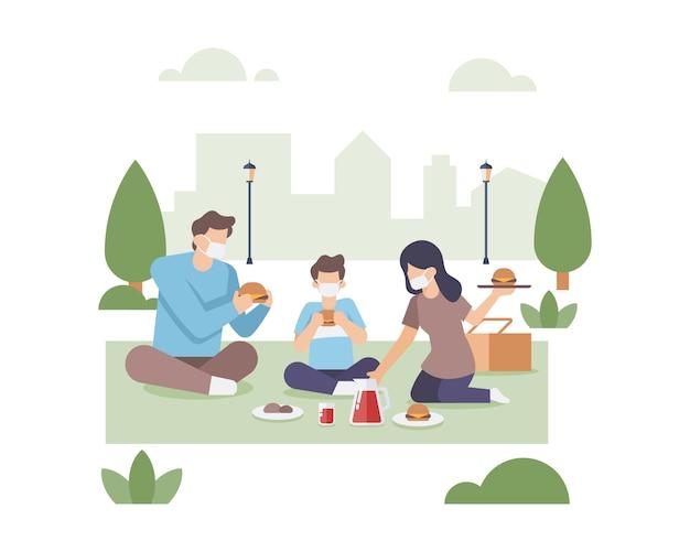 家族がマスクのイラストを着用しながら、公共の都市公園で一緒に食事をする