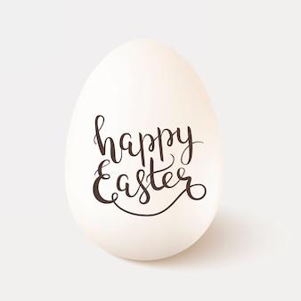 白い背景に分離されたハッピーイースターをレタリングと現実的な白い単一鶏の卵。