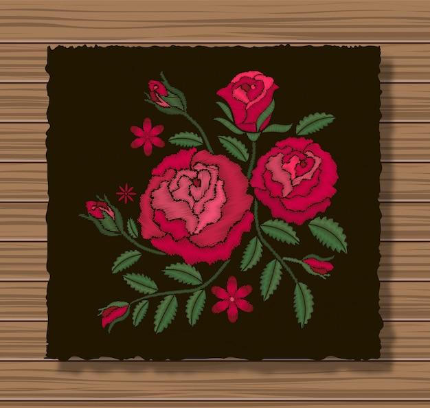 暗いフラップ布と木製のテクスチャ背景にバラと小枝の刺繍ステッチ。