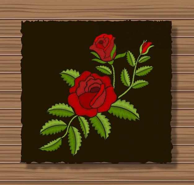 暗いフラップ布と木製のテクスチャに刺繍のバラと小枝