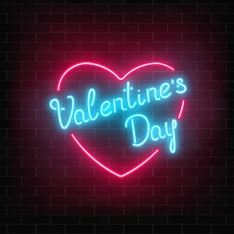 暗いレンガの壁の背景にハートの形で幸せなバレンタインデーネオン輝くお祝いサイン。