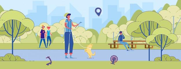 若い男が公園のトレーニング犬でコーギーと遊ぶ