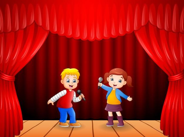 男の子と女の子が彼の手でマイクを使って歌う