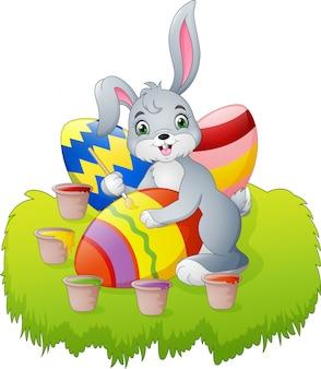Мультяшный пасхальный кролик рисует яйцо