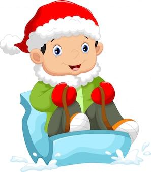 雪の上を滑るサンタ帽子をかぶっている子供