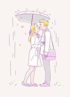 若いカップルが傘の下で雨の中でキスします。