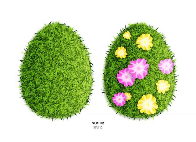 花と緑の草のイースターエッグの背景