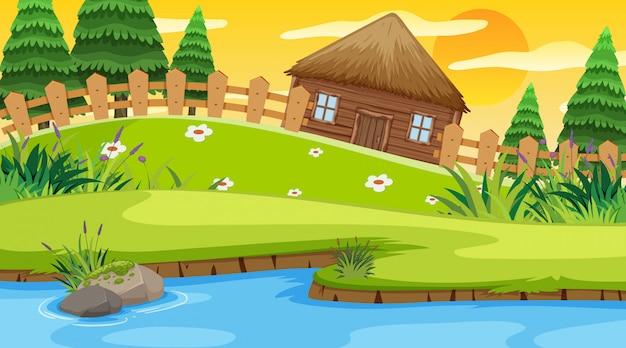 川沿いのフィールドに木製のコテージのあるシーン