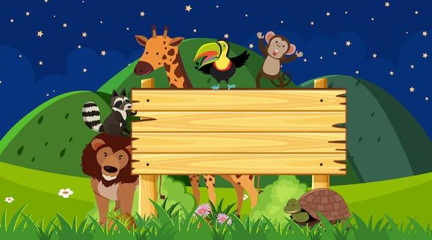 夜の時間で動物と木の看板