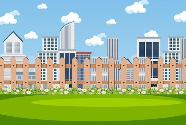 公園の花と後ろの都市の建物の背景シーン