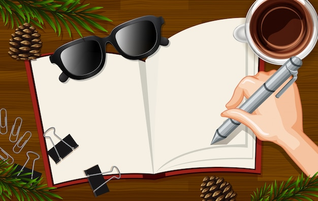 空白の本に手書きのコーヒーカップといくつかの葉の小道具とデスクの背景にクローズアップ