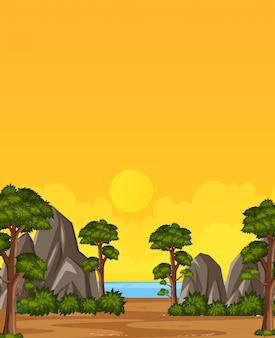 Вертикальная природа сцены или пейзаж сельской местности с деревьями и камнями с видом на пляж и желтый закат небо