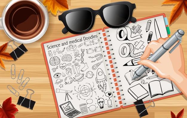 手書きの科学と医療のいたずら書きは、コーヒーとグラスを机の背景にクローズアップ