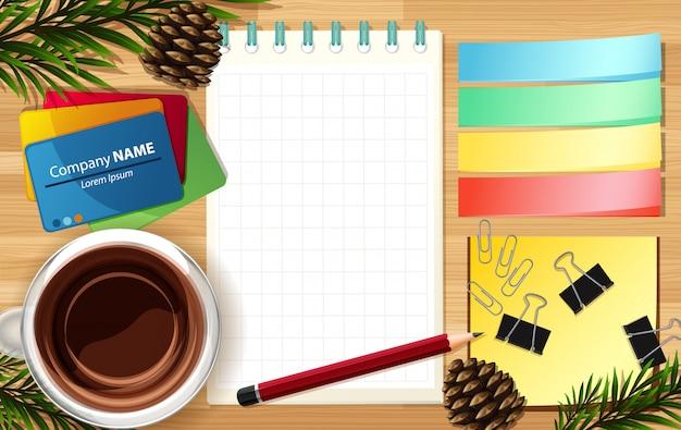 白紙のメモとマークノートをいくつかの葉の小道具とデスクの背景にクローズアップ