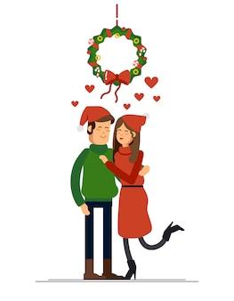 Пара молодых людей на рождество поцелуи под омелой венок. час