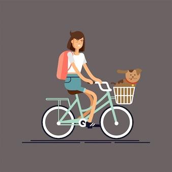 Девушка едет на велосипеде с собакой