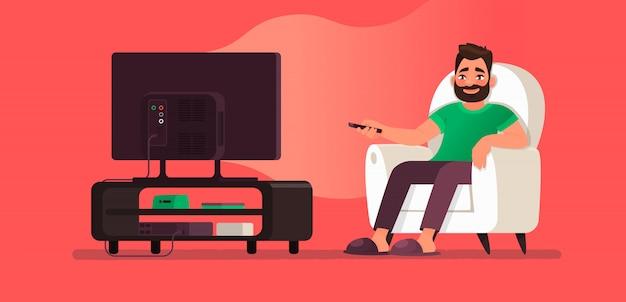 男は椅子に座ってテレビを見ています。お気に入りのテレビ番組や映画を見る