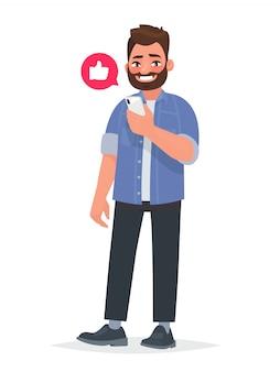 ひげを生やした男は彼の手でスマートフォンを保持しています。ネットワーク、出会い系サイト、ソーシャルネットワークでのコミュニケーション
