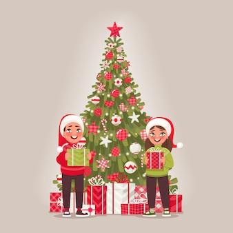 子供と飾られたクリスマスツリー。男の子と女の子がプレゼントを持っています。メリークリスマス、そしてハッピーニューイヤー