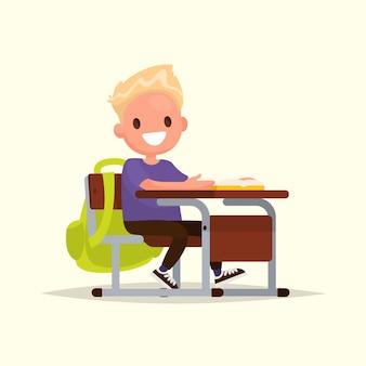 小学校の生徒。男子生徒は学校の机に座っています。