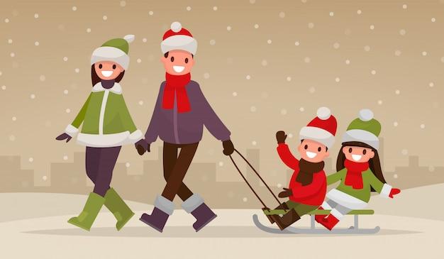 冬の野外を歩いている幸せな家族。両親は子供たちをそりで運ぶ。