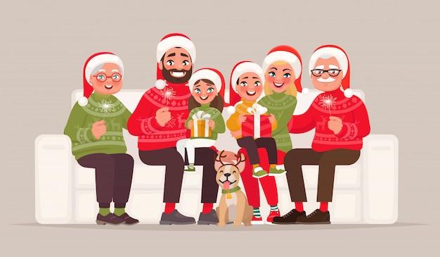 メリークリスマス、そしてハッピーニューイヤー。孤立した背景にソファーに座っていた大家族
