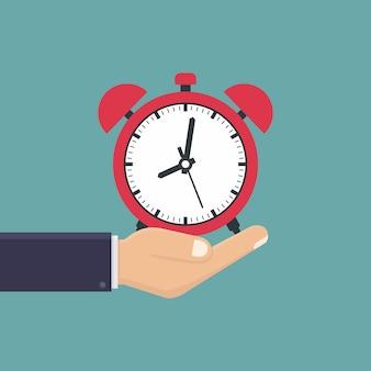 Бизнес рука держать будильник плоский дизайн
