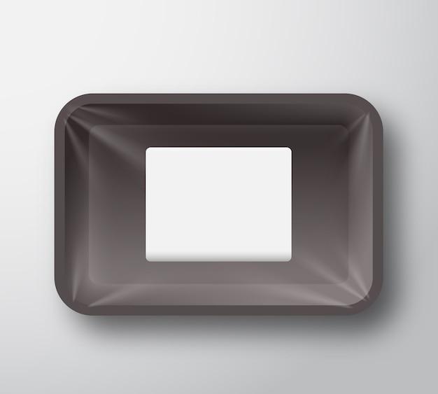 透明なセロハンカバーと透明な白い長方形のステッカーが付いた黒いプラスチック製の空のフードトレイコンテナー