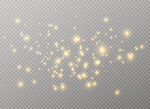 金色の火花と金色の星が特別な光の効果を輝きます。透明な背景の上で輝きます。クリスマスの要約。ほこり。