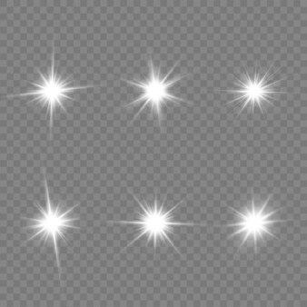 Набор ярких звезд. белый светящийся свет взрывается на прозрачном фоне. прозрачное сияющее солнце, яркая вспышка. сверкающие магические частицы пыли.