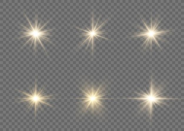 明るい星のセット。透明な背景に黄色の輝く光が爆発します。透明な太陽、明るいフラッシュ。きらめく魔法のダスト粒子。
