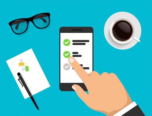 手はチェックリストとスマートフォンを保持し、それをクリックします。予定表が表示された電話。ワークスペースの上面図。トレンディなスタイルのモダンなビジネスワークデスクトップ。図。