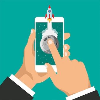 ハンズはロケットの打ち上げでスマートフォンをディスプレイにかざしています。ビジネス製品コンセプト。プロジェクトの立ち上げとイノベーション製品。
